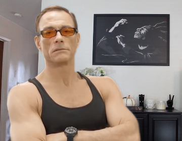 Jean-Claude Van Damme standing with his arms crossed in front a Bob Marley picture hanging on the wall.