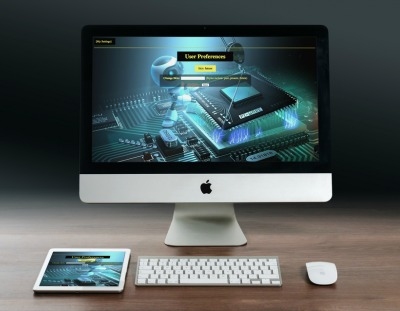 An iMac and iPad displaying a website with a robot working on a computer motherboard.